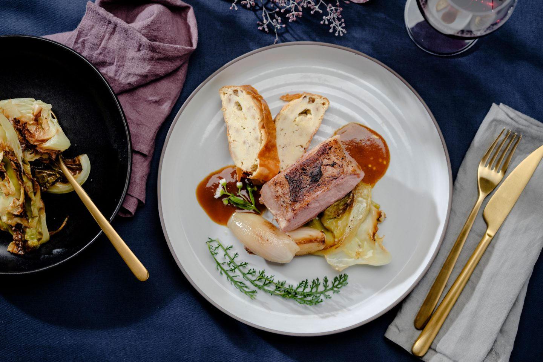 Kalbsbraten auf Ofenkraut mit Schalotten und Griessstrudel auf einem beigen Teller mit einem Glas Rotwein und daneben einem schwarzen Teller mit Kraut aus dem Ofen