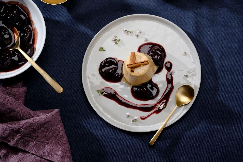 Karamellcreme auf einem hellen Teller mit Dörrzwetschken angerichtet und Blüten dekoriert
