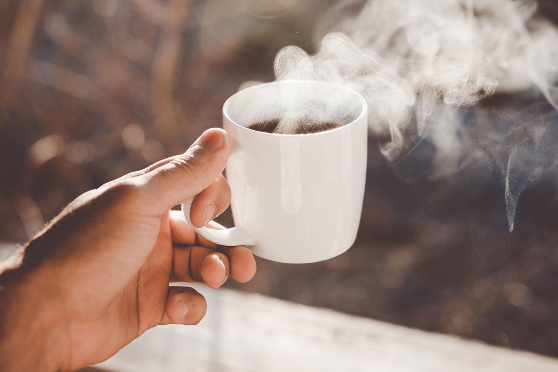 eine Hand hält eine Tasse mit dampfendem Kaffee