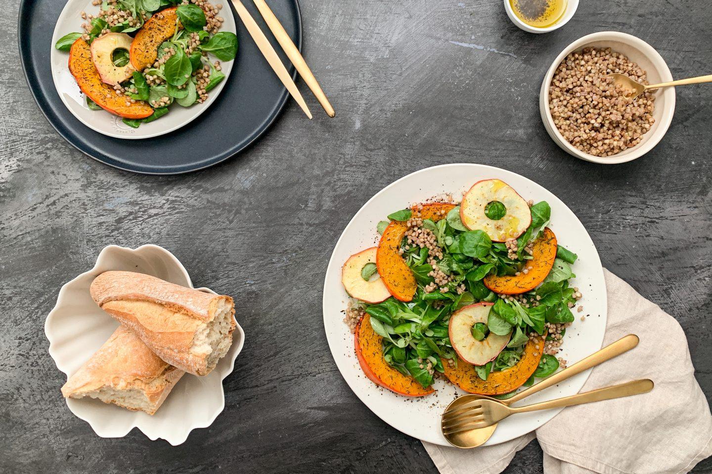 Kürbis-Apfelsalat mit knusprigen Buchweizen auf 2 Tellern angerichtet mit Baguette und goldenem Besteck