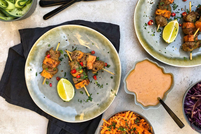Satay-Spiesse vom Reh mit Süsskartoffel-Würfeln und Erdnusssauce auf einem rustikalen, grünlcihen Teller mit Limettenspalte