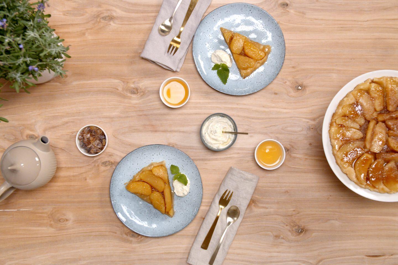 2 Stück Tarte Tatin auf hellblauen Tellern, daneben der ganze Kuchen auf einer weißen Etagere