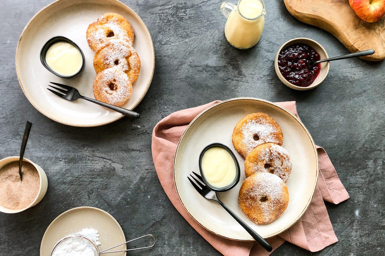 2 Portionen gebackene Apfelradeln auf hellen Tellern mit Vanillesauce in einem schwarzen Schälchen
