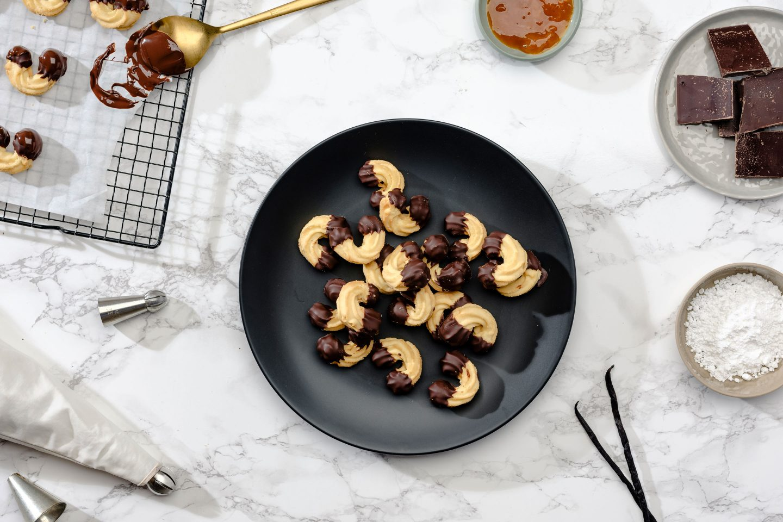 Linzer Kipferl auf einem schwarzen Teller gehäuft mit einem Gitter voller frisch getunkter Kipferl daneben sowie Marmelade in einem Schälchen