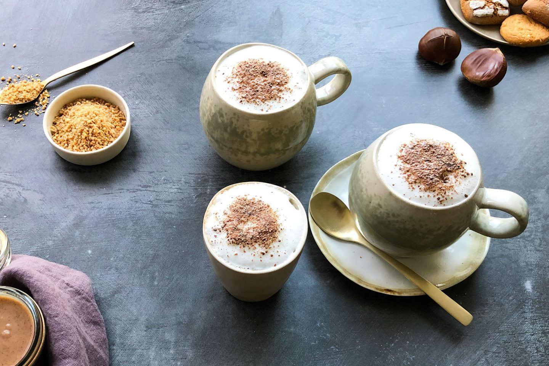 Maroni Spice Latte in 2 bauchigen Tassen mit Salted Caramel Kaffeegewürz getoppt auf dunklem Untergrund