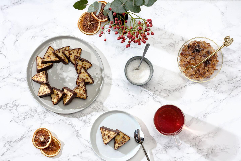 Teekuchen in Kranzform auf einem grauen Teller arrangiert mit einer Tasse Tee, Kandiszucker und Vogelbeeren auf Marmoruntergrund