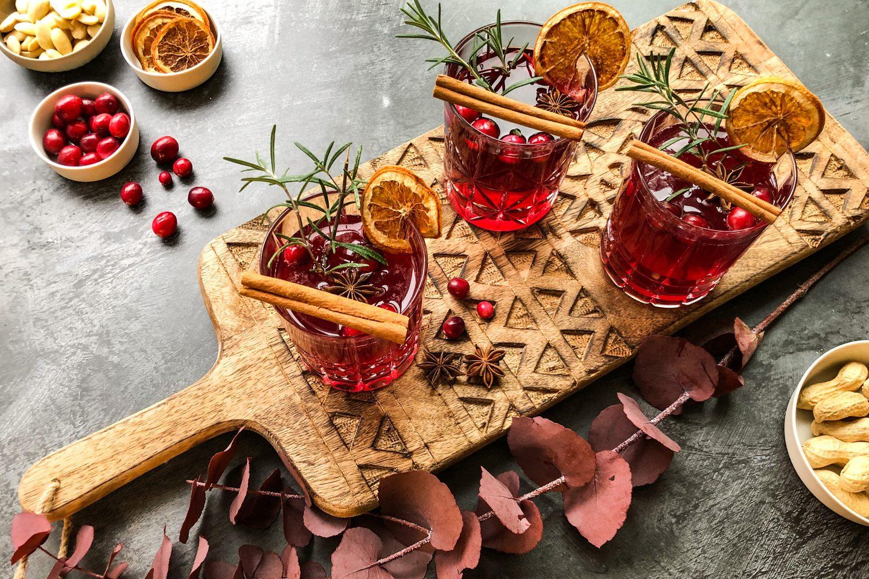 3 Gläser mit Cranberry Spice Mimosas auf einem Holzbrett winterlich verziert mit Zimtstangen, Rosmarinzweigen und getrockneten Orangenscheiben
