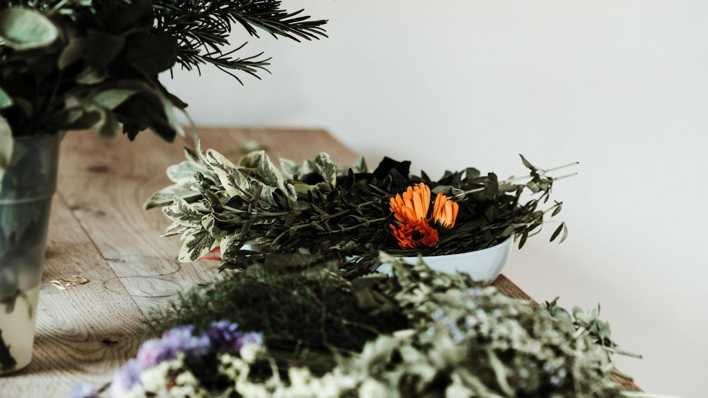 Verschiedene Kräuter in einer Schale und Vase auf einem Holztisch