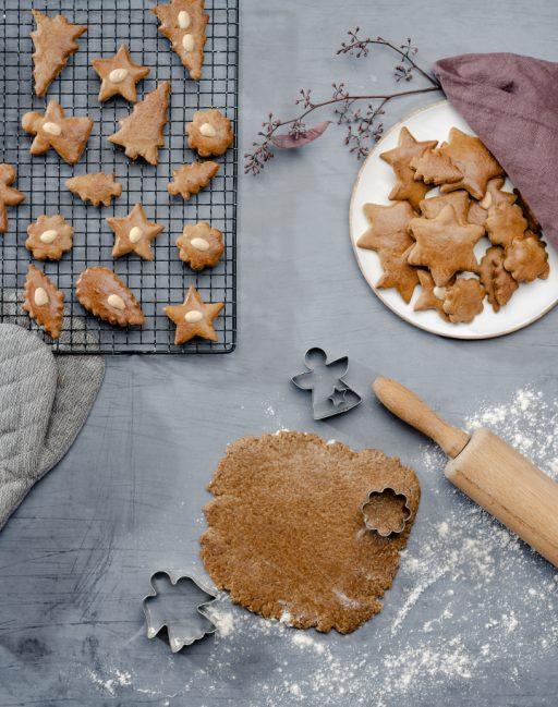 Gebackene Lebkuchen auf einem Kuchengitter und hellem Teller; ausgerollter Lebkuchenteig mit Ausstechern