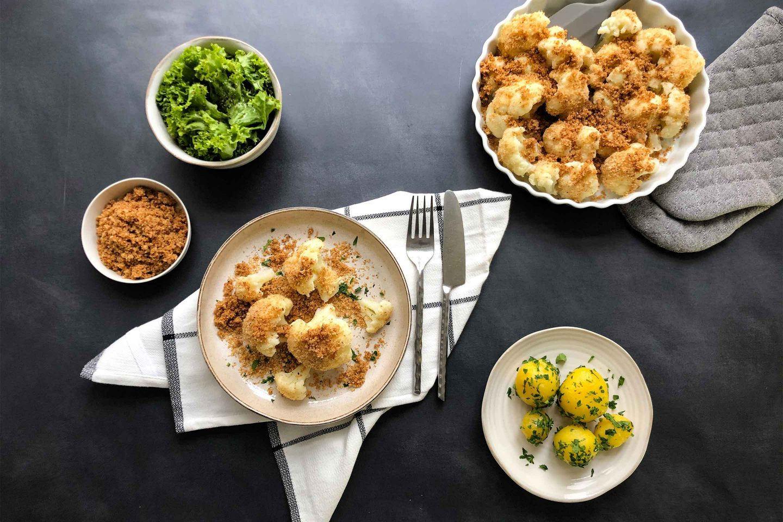 Karfiol Mit Butterbroesel auf einem rustikalen Teller mit grünem Salat und Petersilerdaepfeln als Beilage