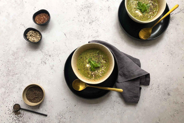 2 Schalen voller Brokkoli-Detox-Suppe auf dunklen Tellern mir goldenen Löffeln