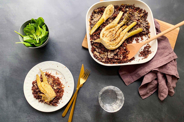 Wildreisauflauf mit Fenchel in einer eckigen Ofenform sowie auf einem Teller angerichtet mit goldenem Besteck und grünem Salat in einem Schälchen