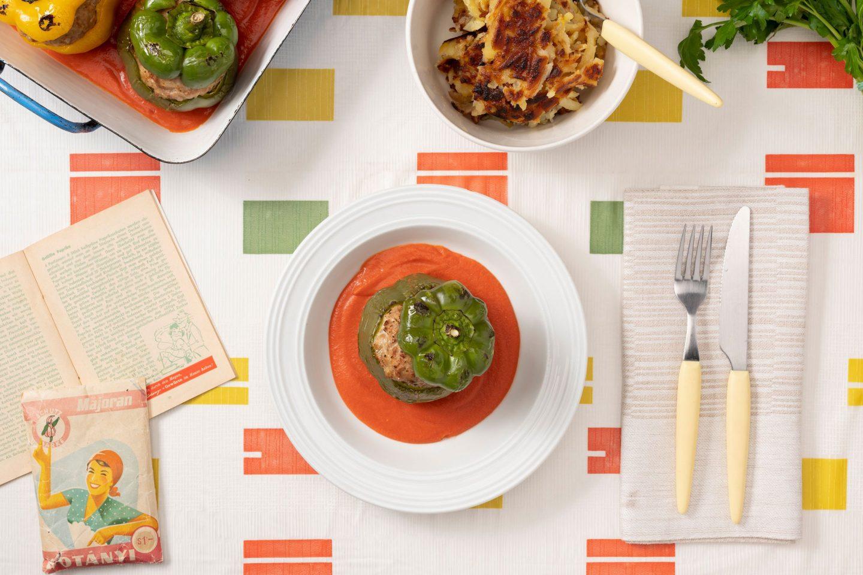 Bunte, gefüllte Paprika in einer Ofenform mit Tomatensauce, geröstete Kartoffeln als Beilage und ein weißer Teller mit einer grünen Paprika auf einem Tischtuch mit typischem fünfziger Jahre Muster.