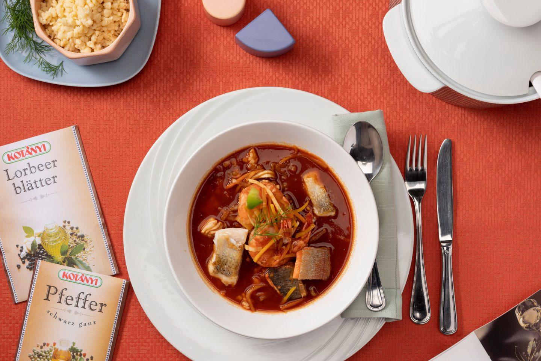 Eine Suppenschüssel mit Deckel voller schmackhafter Fische und Krustentiere in Paprikasud und im Zentrum ein weißer Teller mit einer Portion davon sowie eine rosafarbene Schüssel voller Tarhonya auf einem puderfarbenen Tischtuch. Daneben liegen 2 Briefverpackungen aus den neunziger Jahren.