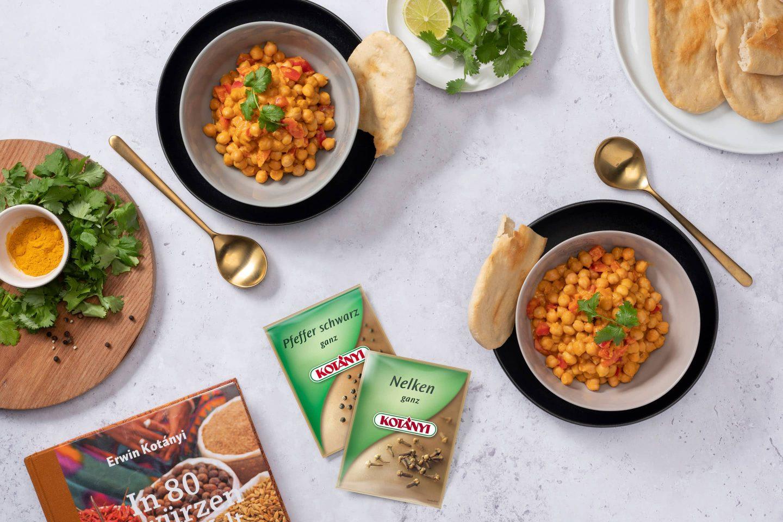 Kichererbsen-Curry in zwei cremefarbenen Schüsseln mit Koriander garniert, daneben ein Teller mit Naan und zwei Kotányi-Biefverpackungen aus den 2000er Jahren.