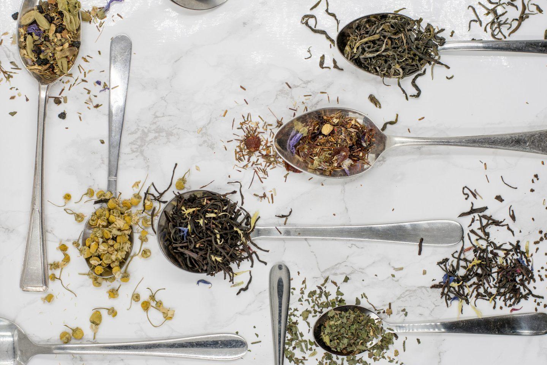 verschiedene Löffel mit Gewürzen und getrockeneten Kräutern für Tee auf einer Marmorfläche