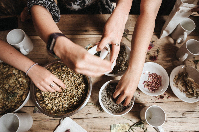 Die Hände von 3 Frauen mischen Tee aus getrockneten Kräutern und Blüten zusammen