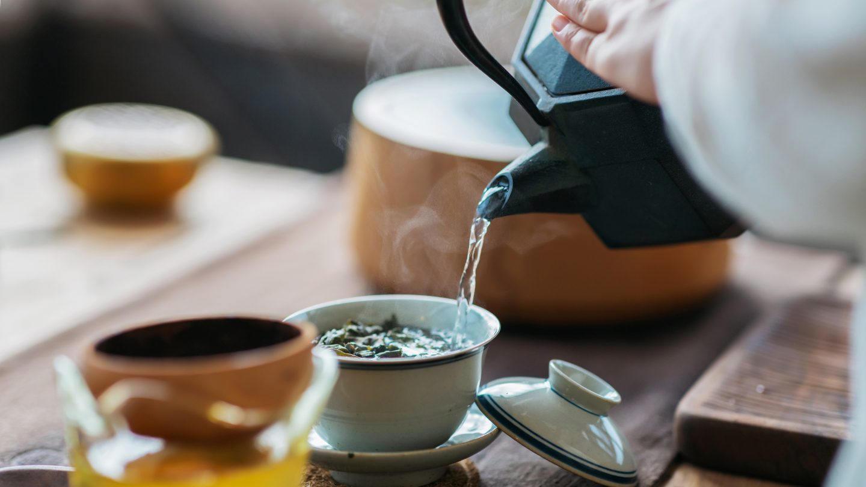 Frau gießt Tee aus einer schwarzen Kanne in eine helle Schale