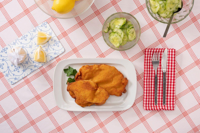 2 Wiener Schnitzel auf einem rechteckigen Teller, mit Gurkensalat in einem gläsernen Schälchen, auf rot-weiß-karierter Tischdecke