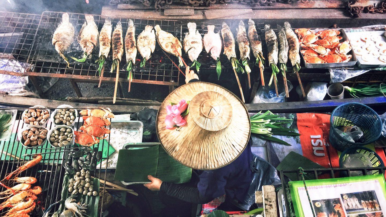 eine thailändische Köchin bereitet Gerichte in ihrem Boot auf den Klongs zu