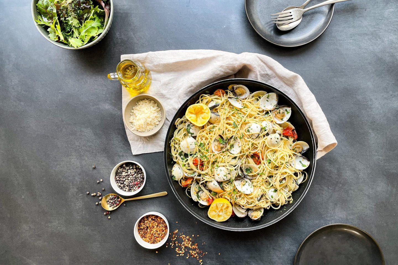 Eine Schüssel mit Pasta Vongole auf einem Geschirrtuch mit Salat und Gewürzen.