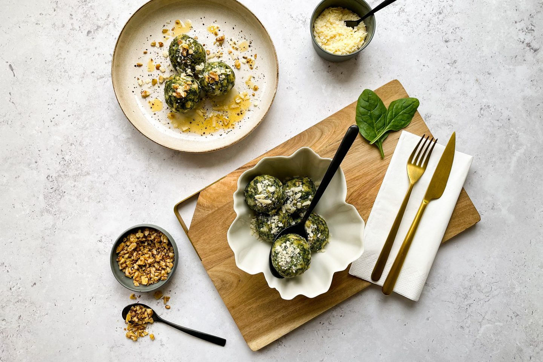 Schmackhafte Spinatknödel am Tisch mit Nussbutter, Besteck und Gewürzen.