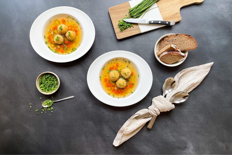 Zwei Schalen Gemüsesuppe und Bröselknödel neben einem Brett mit Schnittlauch.