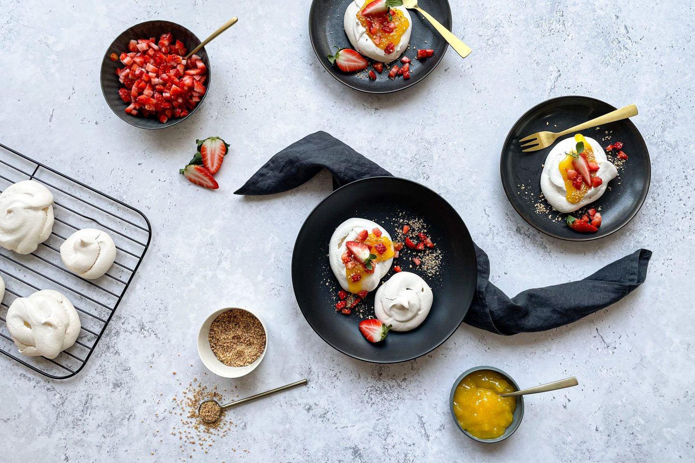 Schmackhafte Mini Pavlovas mit Lemon-Curd und Granatapfelkernen auf zwei Tellern