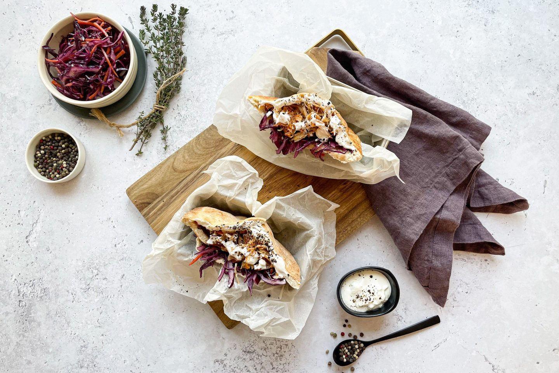 Ein aromatisches Pulled-Chicken-Sandwich mit Coleslaw, Kräuter und Pfeffer.