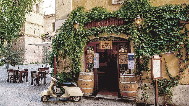 Eine Vespa steht vor einem kleinen italienischen Restaurant mit Gastgarten.