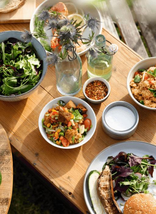 Verschiedene Salate angerichtet auf einem Tisch im Freien