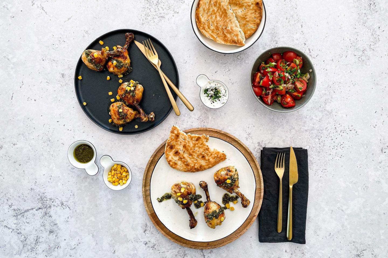 Gegrillte Chicken Drumsticks serviert mit Mais Chimichurri und frischem Brot.