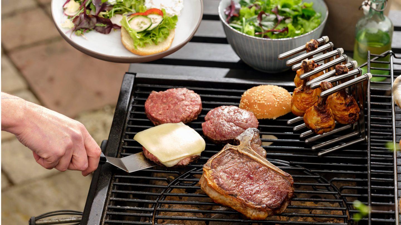Burger Pattys, Hühnerkeulen und Kotelette auf dem Grill