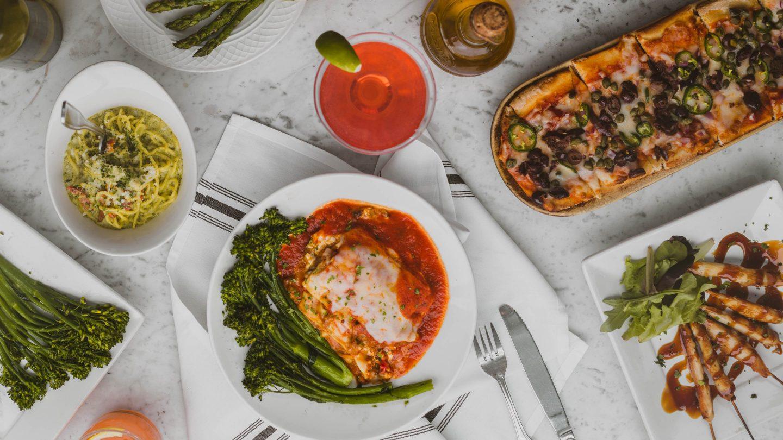 Diverse traditionelle italienische Gerichte zum Abendessen am Esstisch.