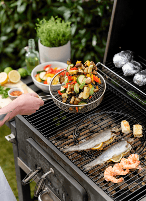 Grillgemüse, Fisch, Grillkäse und Kartoffeln auf einem Grill