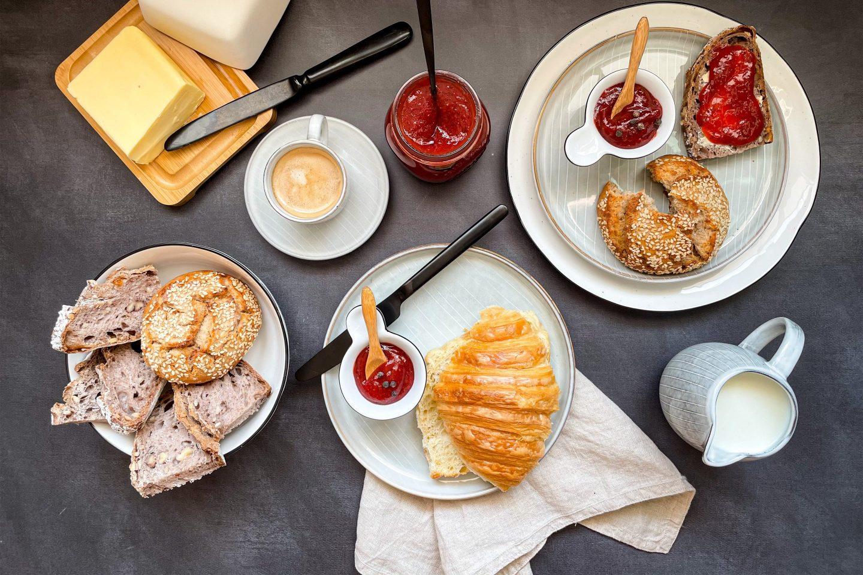Ein gedeckter Frühstückstisch mit pfeffrig würziger Erdbeeren-Minze-Marmelade.