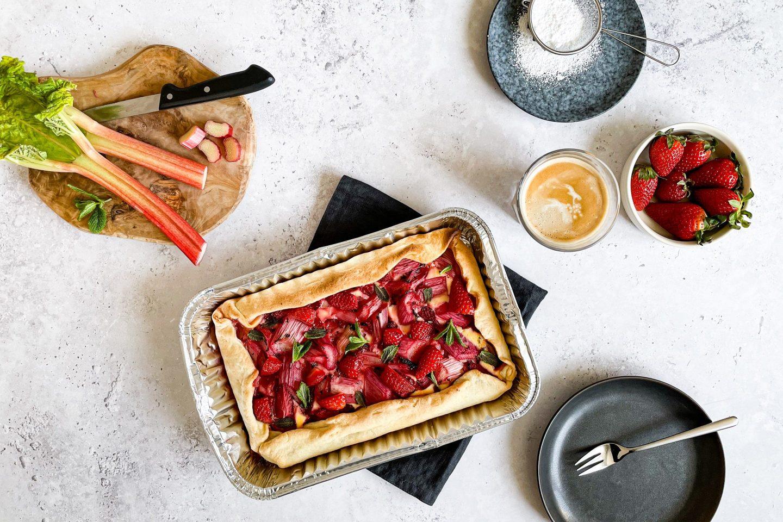 Erdbeer-Rhabarberkuchen vom Grill mit Topfen und gerebelter grüner Minze.