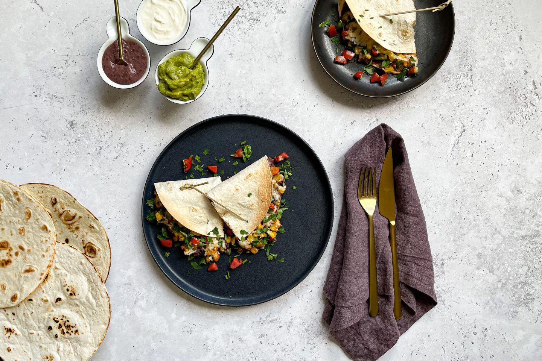Bunte Hühnchen-Quesadillas mit Gemüse und dreierlei mexikanischen Dips.