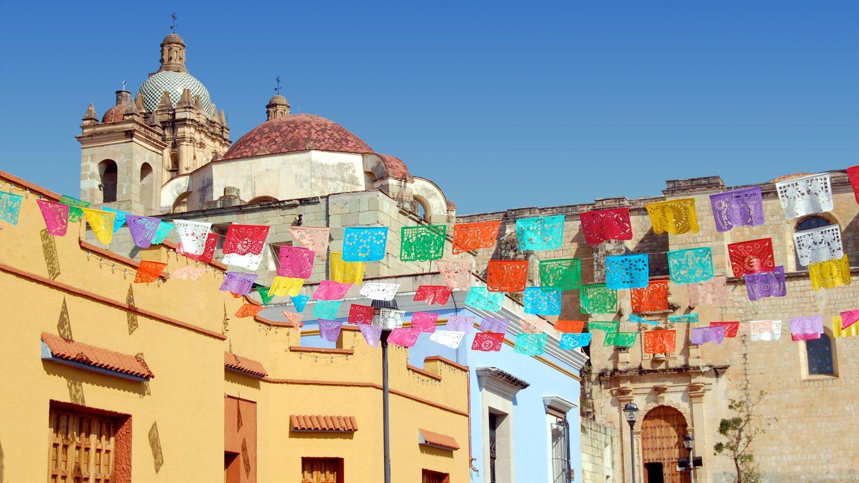 Eine Stadt in Mexiko mit vielen bunten Fahnen an den Häusern.