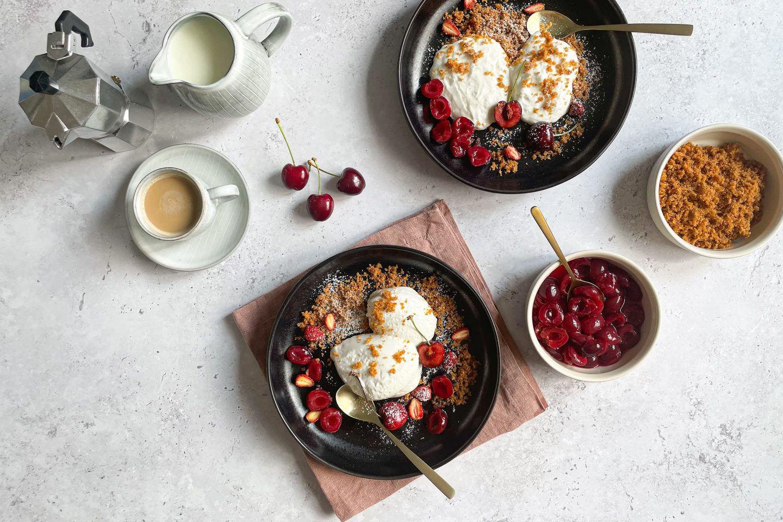 Zwei Portionen kalte Topfennockerl mit frischem Kirschkompott und Kaffee.