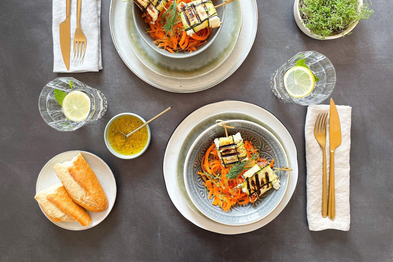 Zwei Portionen Feta-Taler im Zucchinimantel auf Karottennudeln mit Baguette.