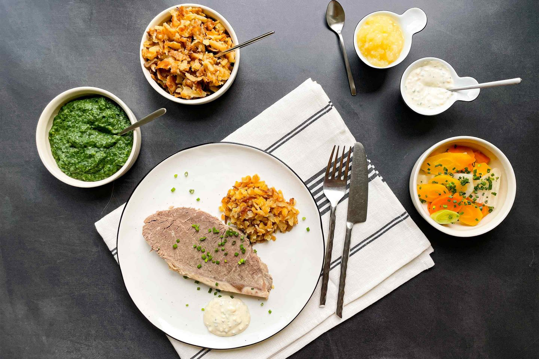 Schmackhafter Tafelspitz mit Röstkartoffel, Schnittlauchsauce und Wurzelgemüse.
