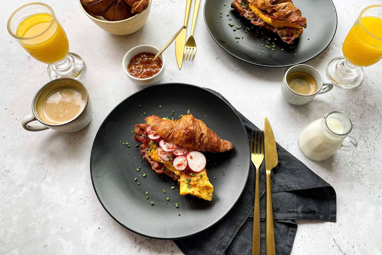 Ein Frühstückstisch mit pikant gefüllten Croissants, Kaffee und Orangensaft.