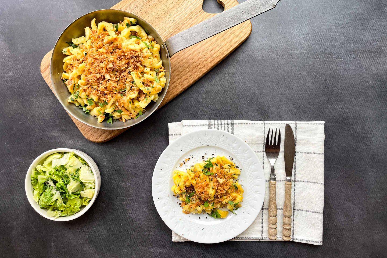 Eine Pfanne mit Käsespätzle und eine Portion am Teller mit Beilagensalat.