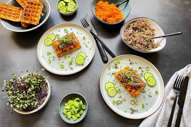 Pulled Goose und orientalischer Salat auf Waffeln mit Kresse und Gurkenscheiben.