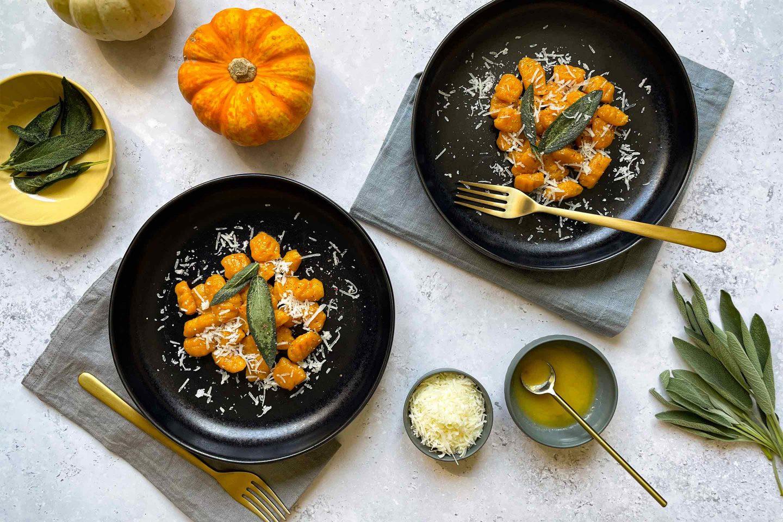 Zwei Portionen Kürbis-Gnocchi mit feinem Salbeibutter und Pecorino Käse.